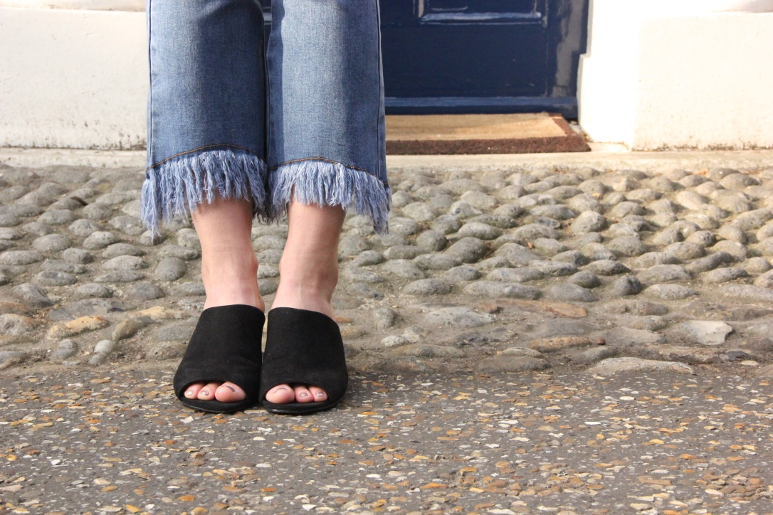 Black mules and frayed hems