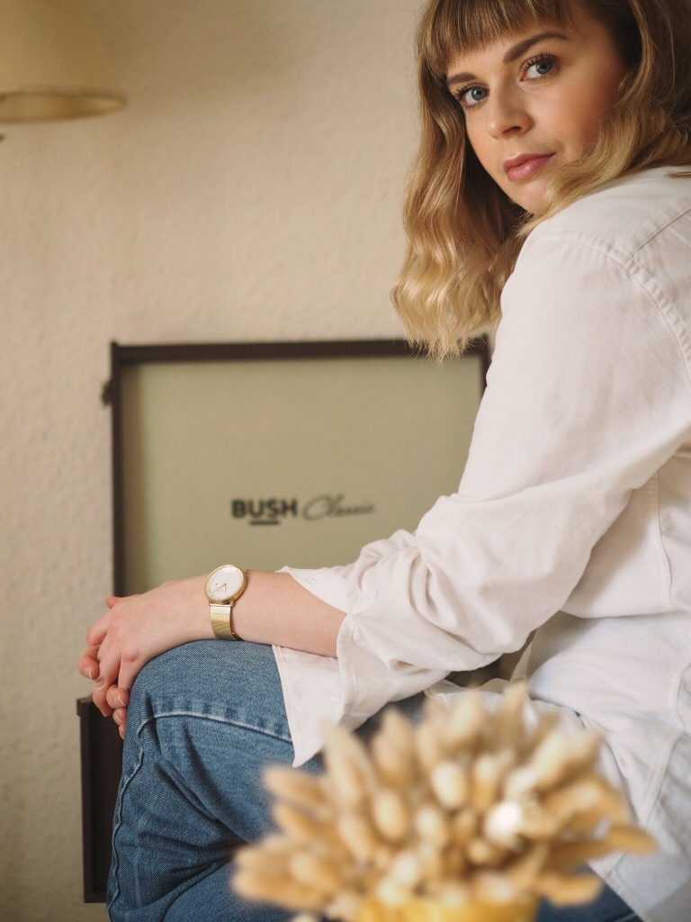 Elevated basics outfit of blue jeans, oversized white shirt and gold details
