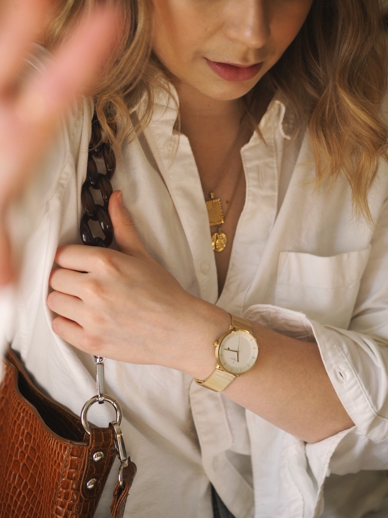 Close up of Nordgreen the Philosopher gold watch with white shirt and gold necklaces